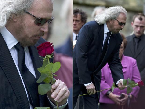 Barry Gibb, único integrante vivo dos Bee Gees, beija uma flor antes de jogá-la no caixão aoo corpo de seu irmão Robin (Foto: AP/Alastair Grant)