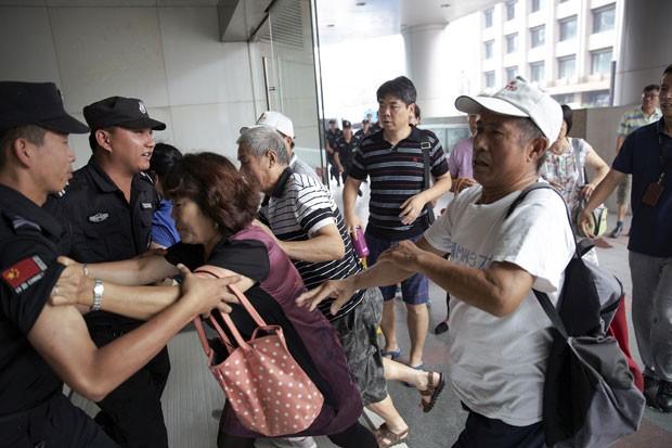 Familiares de passageiros do voo MH370 empurram policiais na entrada do prédio onde fica o escritório da Malaysia Airlines em Pequim no dia 5 de agosto de 2015; inicialmente os seguranças impediram os parentes de entrar, mas em seguida eles foram autoriza (Foto: Damir Sagolj/Reuters)