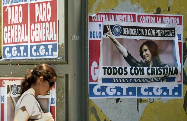 Mulher passa em frente a cartazes a favor de greve geral contra medidas do governo - com panfleto pró-Cristina Kirchner, em 20 de novembro (Foto: Juan Mabromata/AFP)
