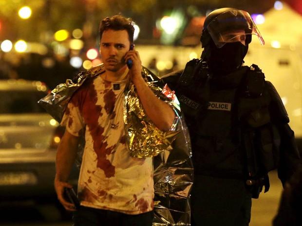 Policial acompanha vítima com camiseta coberta de sangue após ataque terrorista que deixou dezenas de mortos no Bataclan, famosa sala de shows de Paris, na França (Foto: Philippe Wojazer/Reuters)