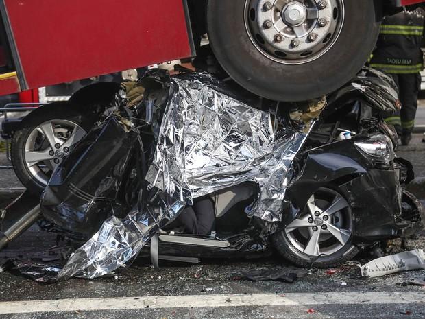 Carro ficou completamente esmagado por ônibus articulado após acidente na Avenida Vereador José Diniz, Zona Sul de São Paulo (Foto: William Volcov/Brazil Photo Press/Estadão Conteúdo)