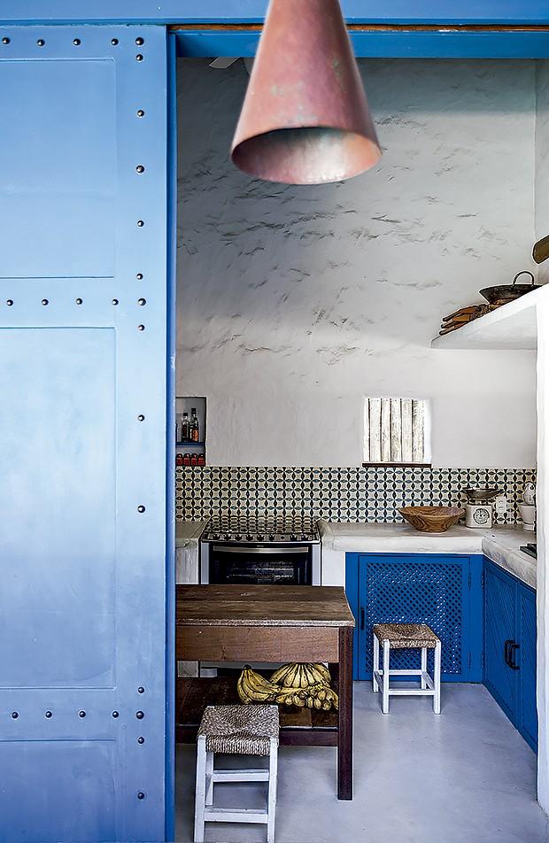 Na cozinha, os ladrilhos comprados em Arraial d'Ajuda foram inspirados nos tunisianos antigos. Mesa e banquinhos vieram de loja de móveis usados (Foto: Marco Antonio/ Editora Globo)