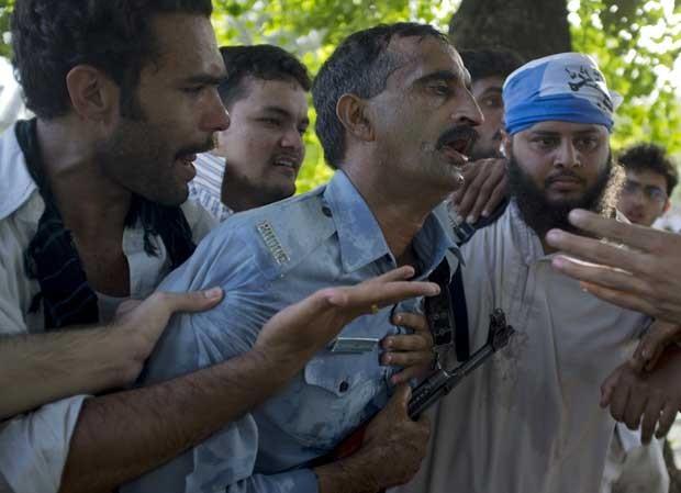 Manifestantes ajudam policial durante protesto no Paquistão nesta quinta-feira (20) (Foto: AP)