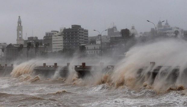Ondas invadem avenida devido aos fortes ventos na capital uruguaia Montevidéu (Foto: Miguel Rojo / AFP)
