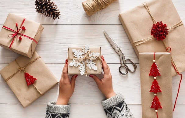 Creative hobby. Woman's hands show christmas holiday handmade present in craft paper with twine ribbon. Making bow at xmas gift box, decorated with snowflake. Scissors on white wooden table, top view. (Foto: Getty Images/iStockphoto)