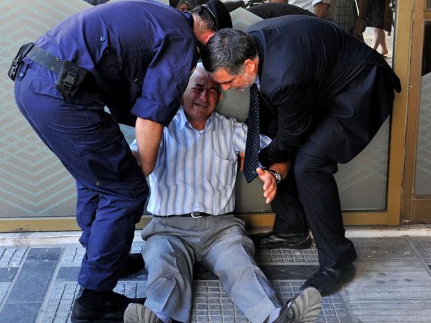 Idoso chora e é amparado em frente a agência bancária em Thessaloniki  (Foto: AFP)