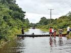 Enchente: cheia de rio interdita rodovia e travessia é feita de canoa