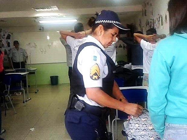 Policial verifica bolsa de uma estudante enquanto outros aguardam revista com mãos na cabeça em sala de aula de escola pública no Paranoá (Foto: Reprodução)