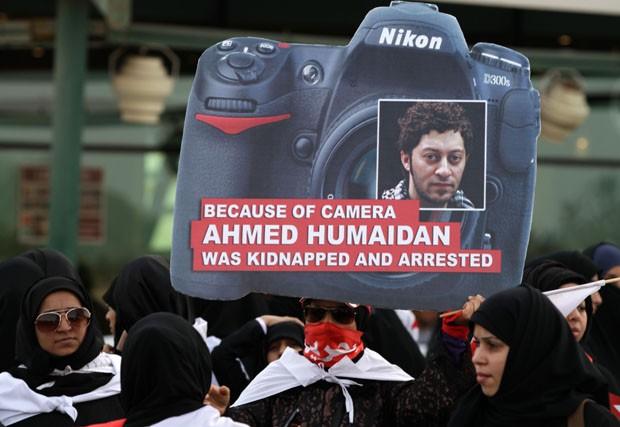 Cartaz em formato de máquina fotográfica mostra o rosto do fotógrafo (Foto: Hasan Jamali/AP)