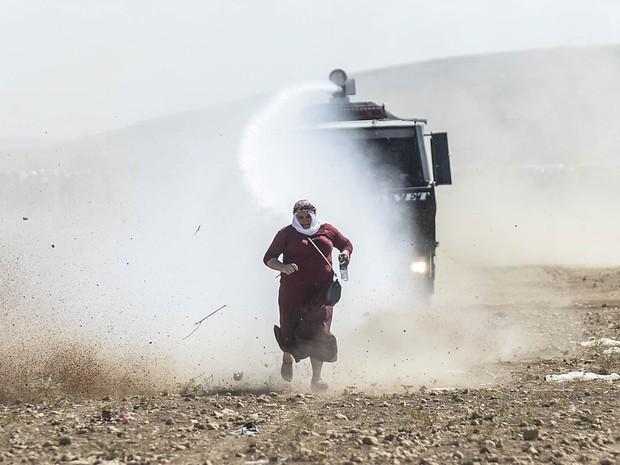 Mulher síria de origem curda corre de blindado turco que usa jato d'água para dispersar migrantes que tentam adentrar a Turquia perto de Suruc. O governo turco informou que cerca de 130 mil sírios cruzaram a fronteira devido à presença do Estado Islâmico (Foto: Bulent Kilic/AFP)