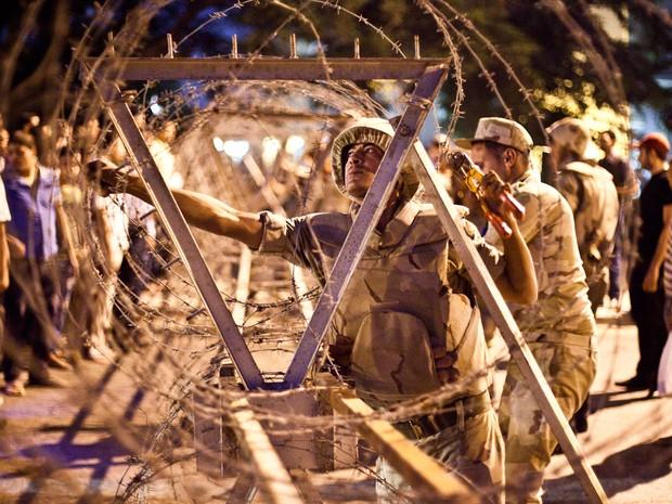 18/8 - Soldados do exército egípcio tiram arame farpado colocado em torno do Supremo Tribunal Constitucional, no Cairo, antes das manifestações planejadas para este domingo. O chefe militar do país prometeu combater protestos violentos. (Foto: Virgnie Nguyen Hoang/AFP)
