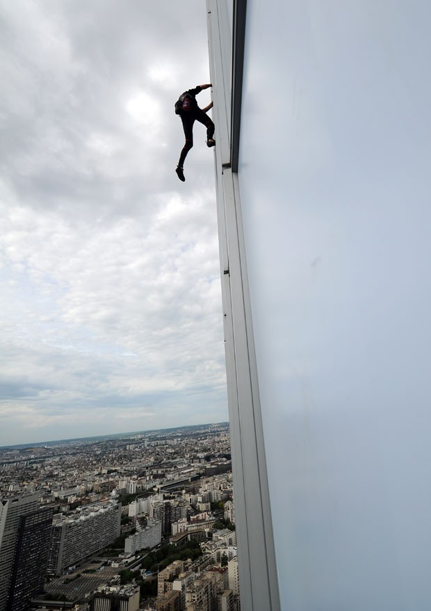 O escalador conhecido como 'homem-aranha' francês, Alain Robert, voltou a chamar atenção nas alturas, subindo sem acessórios de segurança até o topo de um arranha-céu, desta vez o prédio mais alto de seu país. (Foto: Franck Fife/AFP)