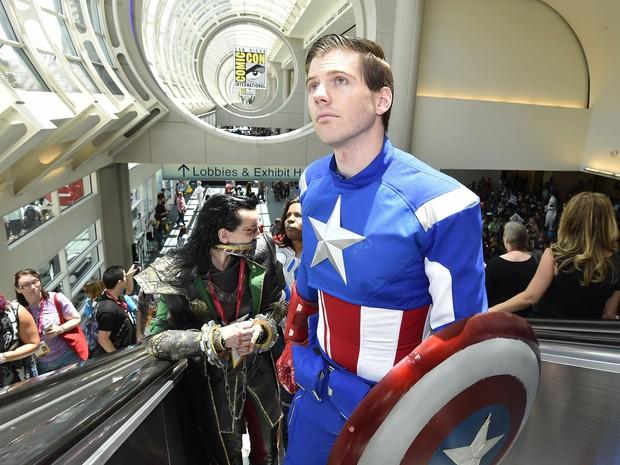 Um desatento visitante fantasiado de Capitão América sobe as escadas rolantes, à frente de Loki, o irmão de Thor, na feira Comic-Con 2014, em San Diego (EUA). (Foto: Denis Poroy/France Presse)