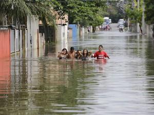 Moradores percorrem rua alagada da comunidade de Jacaraípe, no município de Serra, cerca de 25 km ao norte de Vitória (ES). (Foto: Nelson Antoine/Fotoarena/Estadão Conteúdo)