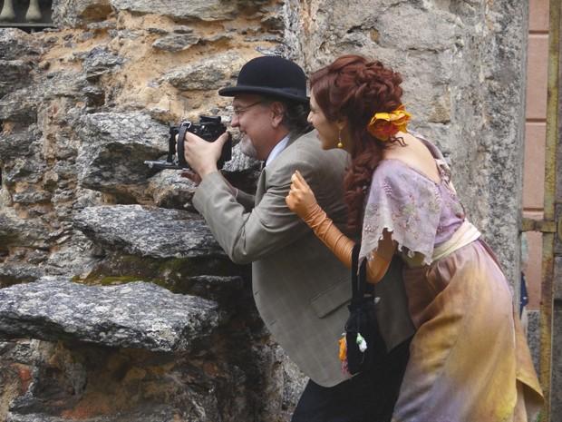 Escondidos, Neusinha e jornalista fotografam Laura (Foto: Lado a Lado/TV Globo)
