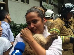 Moradora fica aliviada ao conseguir resgatar o gatinho (Foto: Matheus Rodrigues/G1)