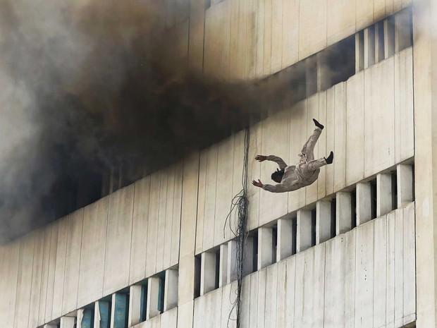 Homem é visto se jogando de prédio em chamas no Paquistão. Pelo menos duas pessoas morreram nesta quinta-feira (9) por causa de um incêndio na cidade de Lahore, no leste do país, após se jogarem do prédio fugindo das chamas, informou a polícia. (Foto: Damir Sagolj/Reuters)