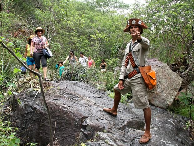 Guia conduz grupo de turistas por trilha na caatinga até a Grota de Angico, local onde o bando de Lampião foi emboscado (Foto: Waldson Costa/G1)