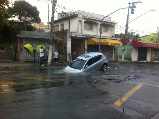 Imagem registrada por leitar mostra carro em cratera quando o nível da água ainda estava alto, alagando parte da rua. (Foto: Henrique Cruz Gomes/VC no G1 )