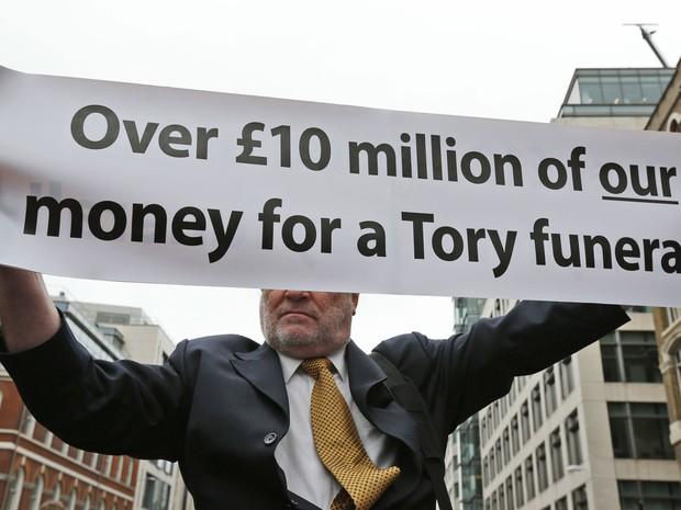 'Mais de 1 milhão de libras do nosso dinheiro para um funeral Tory', diz a faixa de um manifestante contrário às políticas de Thatcher, citando ala conservadora de políticos britânicos (Foto: Lefteris Pitarakis/AP)