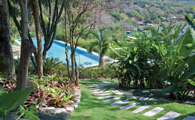 Um caminho de pedras vulcano leva à piscina. Ao acessá-lo, vê-se, do lado esquerdo, um canteiro de bromélias e, no lado oposto, bananeiras e alpínias. Ao fundo, próximo à piscina, palmeira-garrafa e moreias (Foto: Renato Elkis/ Divulgação)