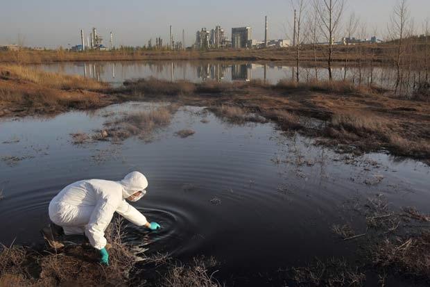Pesquisador do Greenpeace tira amostra do que o grupo diz ser água residual despejada por projeto da mineradora Shenhua me uma região da Mongólia Interior. A foto foi tirada em 26 de abril (Foto: Reuters/Qiu Bo/Greenpeace/)