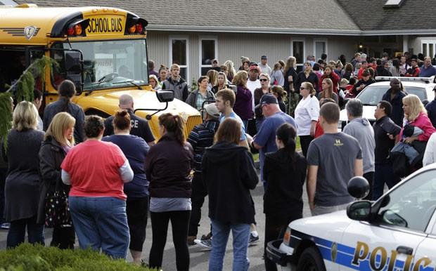 Pais se reúnem em volta de ônibus escolar que tirou parte dos alunos do colégio de Marysville (Foto: AP/Ted Warren)