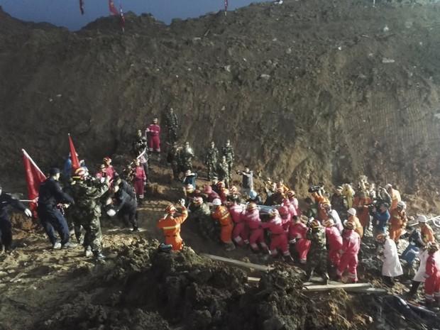 Equipes de resgate carregam sobrevivente de 19 anos após desmoronamento na China (Foto: Reuters/Stringer)
