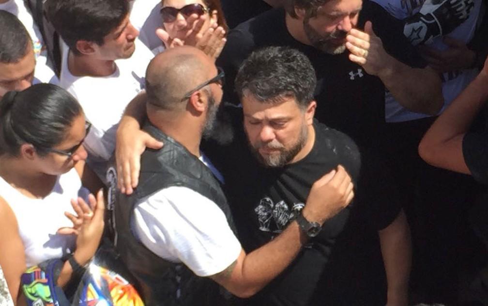 Pai de Miguel é consolado ao lado do jazigo onde o corpo do rapaz foi sepultado (Foto: Matheus Rodrigues/G1)