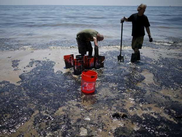 Voluntários enchem baldes de óleo ao longo da costa da Califórnia. (Foto: Lucy Nicholson / Reuters)