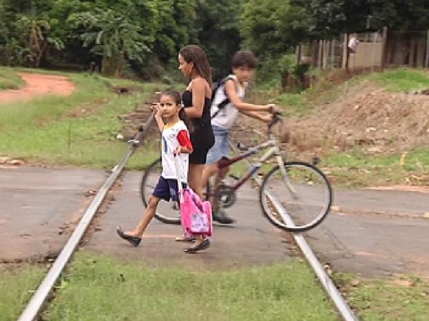 Pessoas passam por trilho de trem em cidade no noroeste paulista (Foto: Reprodução / TV Tem)