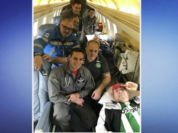 Imagem mostra Henzel e Ruschel (ao fundo) em avião da FAB, acompanhado de médicos (Foto: Reprodução/RBSTV)