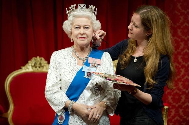 Lisa Burton usa um pincel para dar os últimos retoque à rainha Elizabeth II de cera (Foto: Leon Neal/AFP)