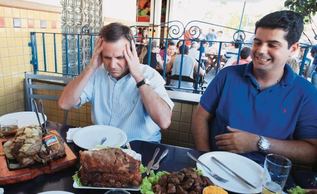 """TESTANDO OS PRÓPRIOS LIMITES Paes com o assessor David Carlos, degustando costelinhas e a tábua """"infarto completo"""",  no bar Cachambeer (Foto: Evandro Teixeira/ÉPOCA)"""