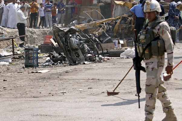 Soldado americano em vistoria a local destruído por carro-bomba em Basra, Iraque, na onda de atentados que atingiu o país neste domingo (Foto: Nabil al-Jurani/AP)
