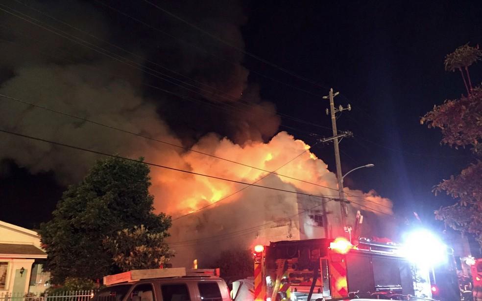 Fogo atingiu um armazém onde estava sendo realizada uma festa em Oakland, na Califórnia, na madrugada de sábado (3) (Foto: @seungylee14 via AP)