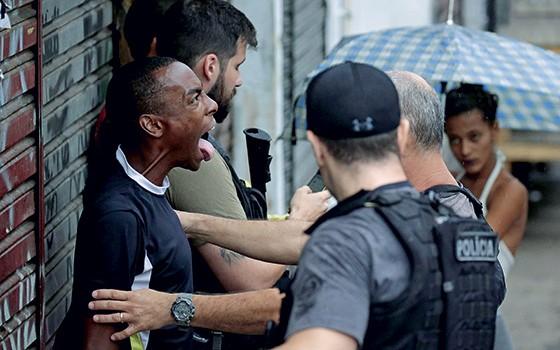 EMPAREDADOS A polícia revista pessoas em mais uma semana de violência intensa no Rio. A estratégia atual de segurança pública está fracassando (Foto: Gabriel De Paiva/ Agência O Globo)