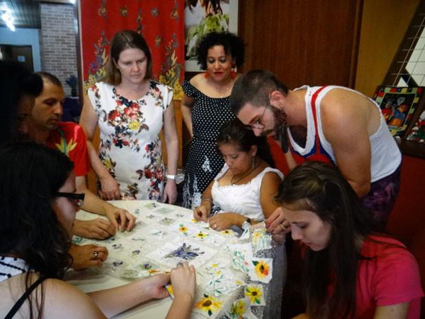 Grupo que participa dos encontros semanais na universidade prepara o painel que será exposto durante o seminário (Foto: Regina Santomauro / G1 Campinas)