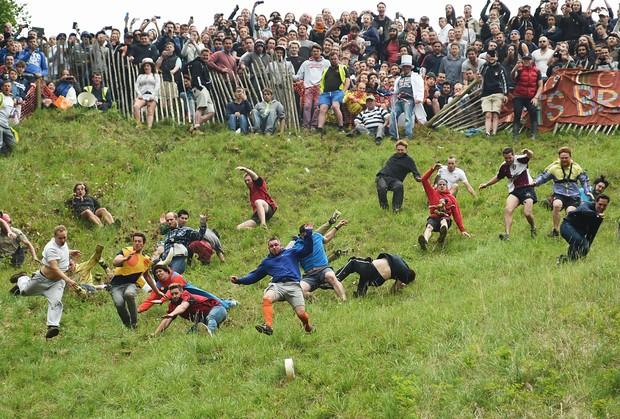 Dezenas de pessoas encararam a tradicional corrida do queijo na Inglaterra (Foto: Joe Giddens/PA/AP)