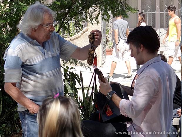 Martin recebe uma encomenda na praça e leva um susto (Foto: Malhação / TV Globo)