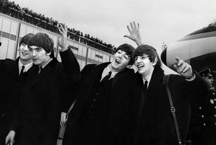 John Lennon, Ringo Starr, Paul McCartney e George Harrison desembarcam no aeroporto John F. Kennedy Airport, em Nova York, EUA, onde são recebidos por multidão de fãs em fevereiro de 1964