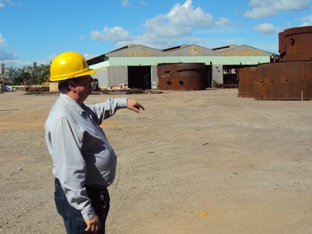 Flaviano Gaggiato, diretor-presidente da Viga Caldeiraria, mostra peças paradas no pátio da empresa (Foto: Patrícia Belo/G1)