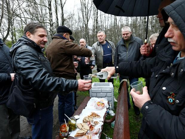 Um grupo de homens também se reuniu também em Minsk, na capital da Bielorrússia, beberam vodka para lembrar os amigos mortos na tragédia de Chernobyl nesta terça-feira (26) (Foto: Vasily Fedosenko/ Reuters)