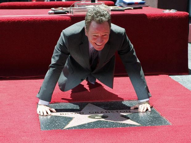 O ator Bryan Cranston, protagonista de 'Breaking bad', brinca de fazer flexão sobre sua estrela na Calçada da Fama de Hollywood (Foto: Fred Prouser/Reuters)