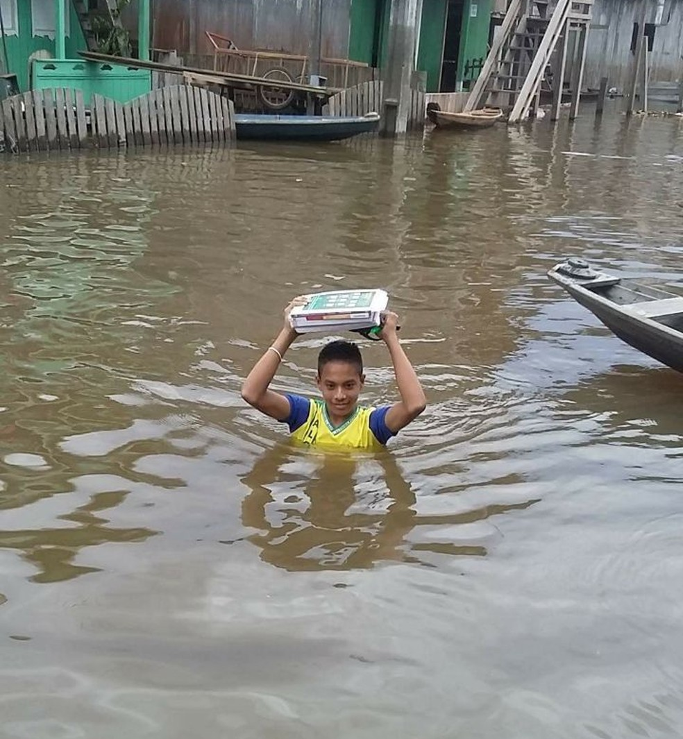 Aluno vai à escola com livros na cabeça (Foto: Reprodução/Rede Amazônica)