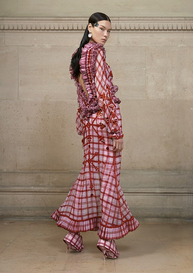 Angelica wears a silk chiffon tartan-print dress embellished with red mirror-effect crystals and delicate plissé soleil at the waist, neck and hem; worn with a printed jersey lace-encrusted jumpsuit (Foto: Givenchy)