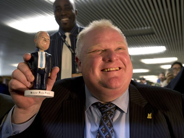 O prefeito de Toronto, Rob Ford, segura sua versão boneco nesta terça-feira (12) na sede da prefeitura (Foto: The Canadian Press, Frank Gunn/AP)