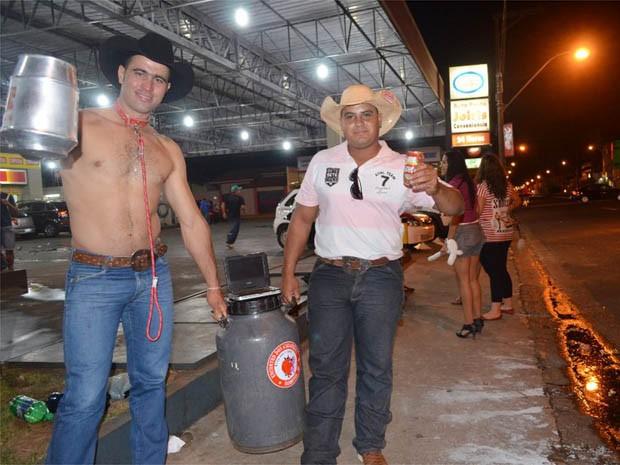 Tiago Pagoto (esquerda) e o amigo Rafael de Melo utilizam galão de leite para gelar cervejas na Avenida 43 em Barretos, SP (Foto: Rodolfo Tiengo/G1)