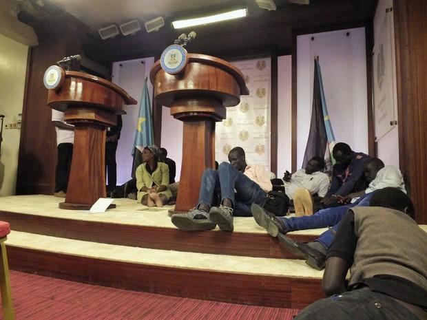 Em foto de sexta-feira (8), jornalistas se abaixam após ouvirem som de tiros durante uma conferência com o presidente Salva Kiir e o vice, Riek Machar (Foto: Stringer / Reuters)