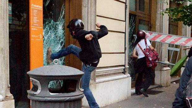 Manifestante depreda fachada durante manifestação contra austeridade realizada em Roma neste sábado (19) (Foto: Alberto Pizzoli/AFP)
